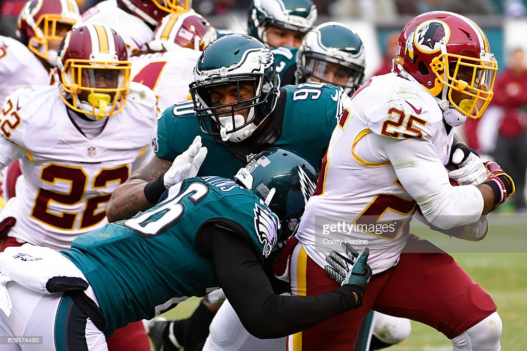 Chris Thompson #25 of the Washington Redskins rushes against Jaylen Watkins #26 and Marcus Smith #90 both of the Philadelphia Eagles as Deshazor Everett #22 of the Washington Redskins looks on at Lincoln Financial Field on December 11, 2016 in Philadelphia, Pennsylvania. The Redskins won 27-22.