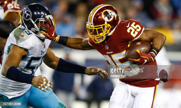 Chris Thompson of the Washington Redskins stiff arms Wesley Woodyard of the Tennessee Titans while running with the ball during the third quarter at...