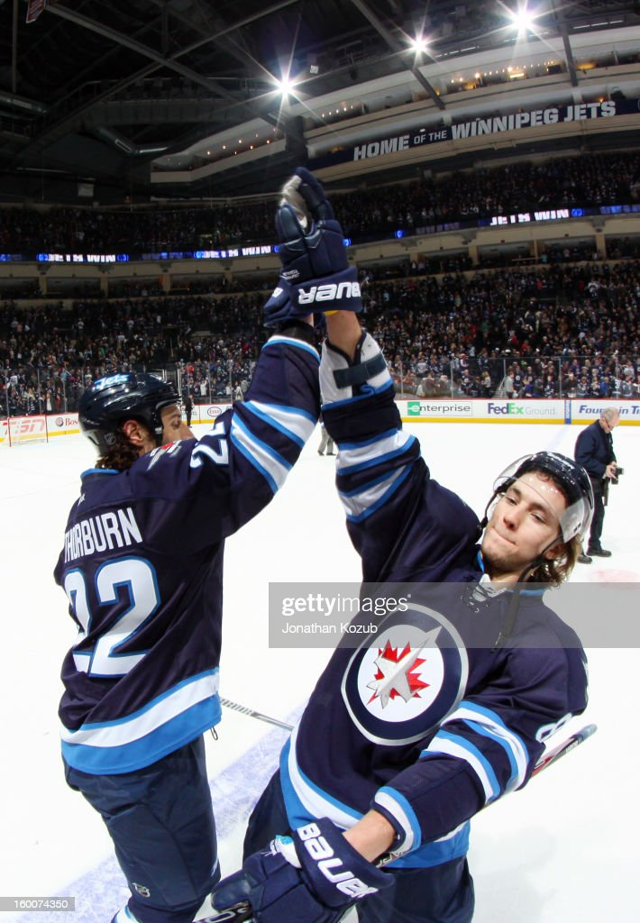 Chris Thorburn #22 and Alexander Burmistrov #8 of the Winnipeg Jets celebrate with a high-five following a 4-2 victory over the Pittsburgh Penguins at the MTS Centre on January 25, 2013 in Winnipeg, Manitoba, Canada.