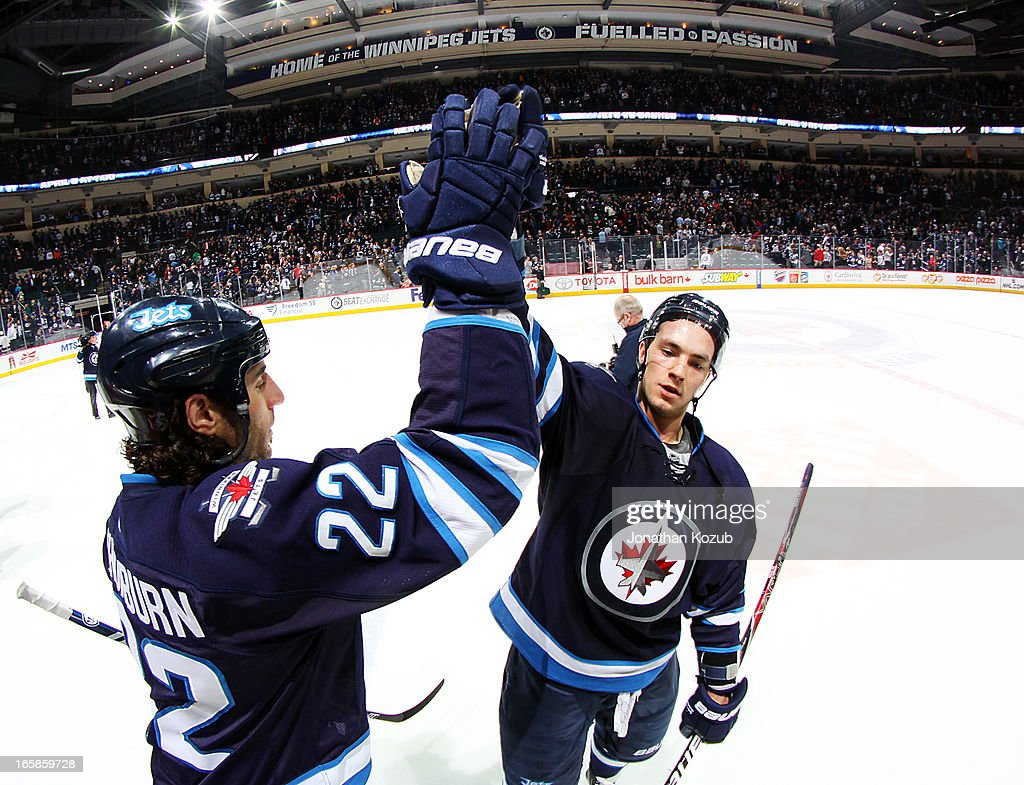Chris Thorburn #22 and Alexander Burmistrov #8 of the Winnipeg Jets celebrate with a high five following a 4-1 victory over the Philadelphia Flyers at the MTS Centre on April 6, 2013 in Winnipeg, Manitoba, Canada.
