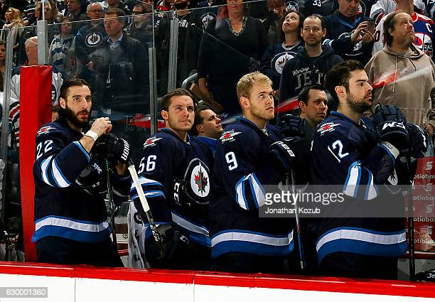 Chris Thorburn Marko Dano Andrew Copp and Drew Stafford of the Winnipeg Jets look on from the bench prior to puck drop against the Florida Panthers...