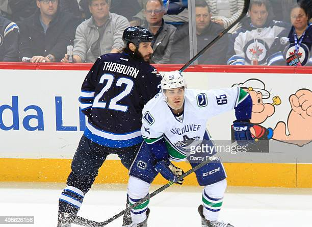Chris Thorburn of the Winnipeg Jets and Alexandre Grenier of the Vancouver Canucks keep an eye on the play during second period action at the MTS...