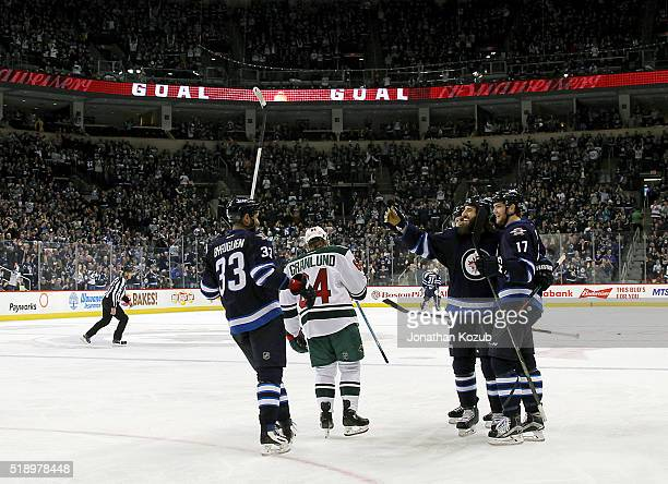 Chris Thorburn of the Winnipeg Jets celebrates his second period goal against the Minnesota Wild with teammates Dustin Byfuglien and Adam Lowry at...
