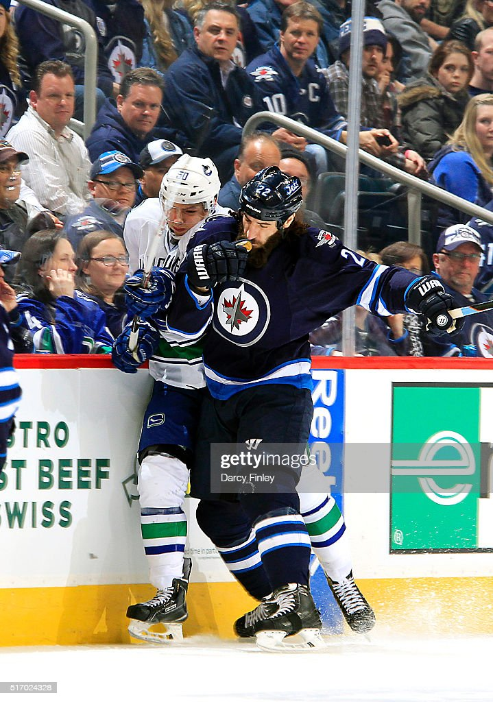 Chris Thorburn #22 of the Winnipeg Jets checks Brendan Gaunce #50 of the Vancouver Canucks into the boards during third period action at the MTS Centre on March 22, 2016 in Winnipeg, Manitoba, Canada.