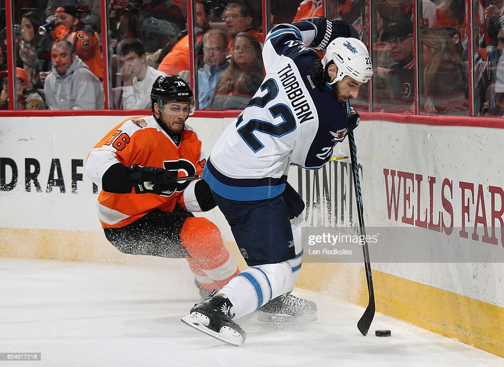 Chris Thorburn #22 of the Winnipeg Jets, playing in his 700th NHL game, controls the puck along the boards while being pursued by Chris VandeVelde #76 of the Philadelphia Flyers on November 17, 2016 at the Wells Fargo Center in Philadelphia, Pennsylvania. The Flyers went on to defeat the Jets 5-2.