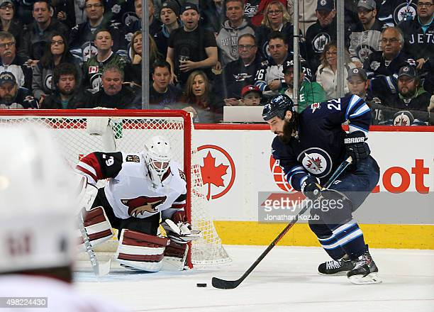 Chris Thorburn of the Winnipeg Jets plays the puck as goaltender Anders Lindback of the Arizona Coyotes guards the net during third period action at...