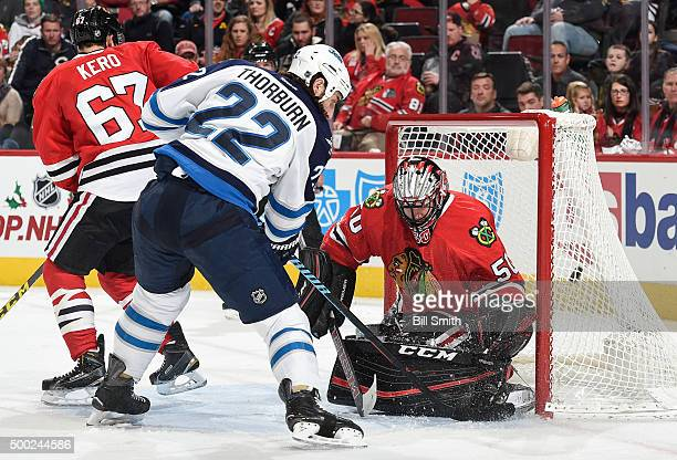Chris Thorburn of the Winnipeg Jets scores on goalie Corey Crawford of the Chicago Blackhawks in the second period of the NHL game at the United...