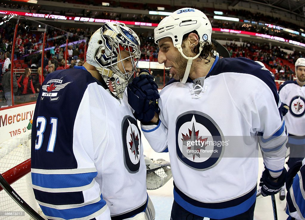 Chris Thorburn #22 of the Winnipeg Jets, who scored the game-winning goal, congratulates Ondrej Pavelec #31 on a victory over the Carolina Hurricanes after an NHL game at PNC Arena on February 4, 2014 in Raleigh, North Carolina.