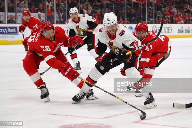 Chris Tierney of the Ottawa Senators tries to avoid the stick of Danny DeKeyser of the Detroit Red Wings during the first period at Little Caesars...