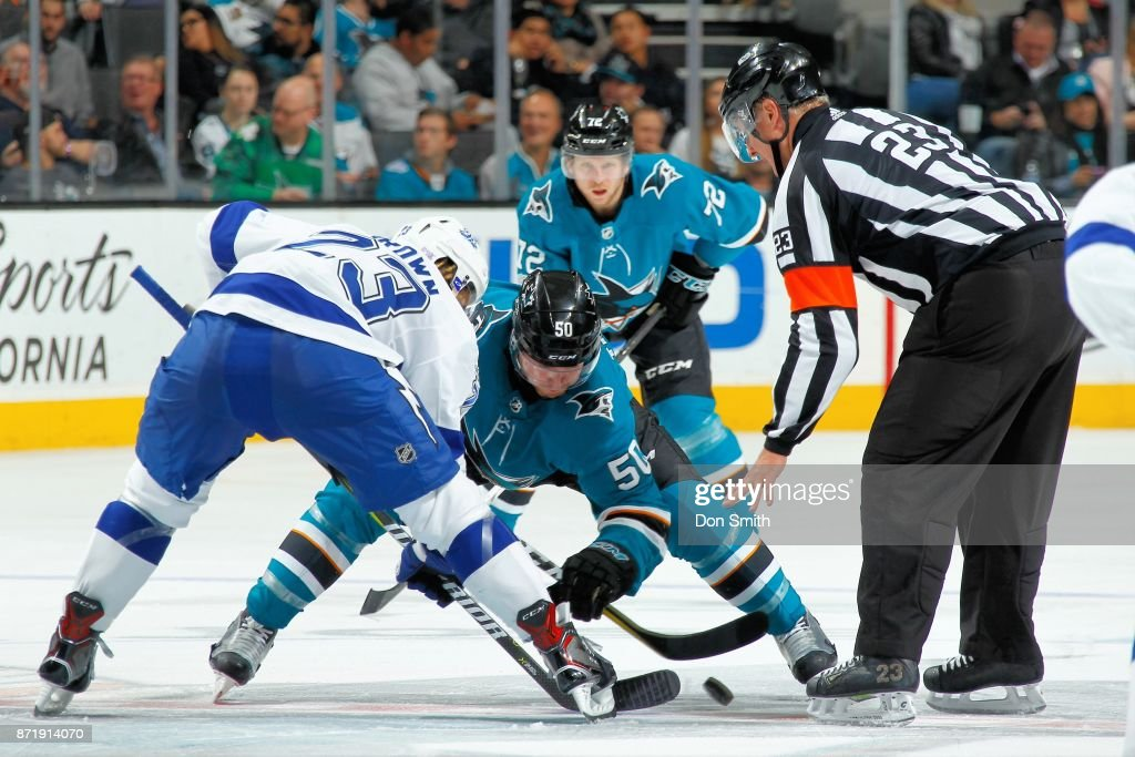Chris Tierney #50 of the San Jose Sharks and J.T. Brown #23 of the Tampa Bay Lightning faceoff as Tim Heed #72 of the San Jose Sharks looks on at SAP Center on November 8, 2017 in San Jose, California.