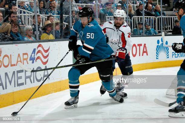 Chris Tierney of the San Jose Sharks keeps the puck away from Matt Nishkanen of the Washington Capitols at SAP Center on March 10 2018 in San Jose...