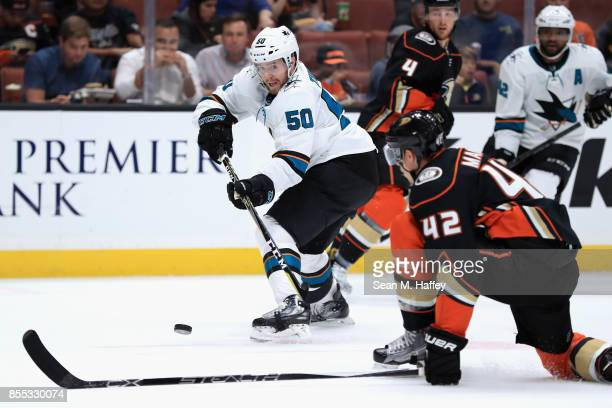 Chris Tierney of the San Jose Sharks passes the puck past Josh Manson of the Anaheim Ducks during the second period of a preseason game at Honda...