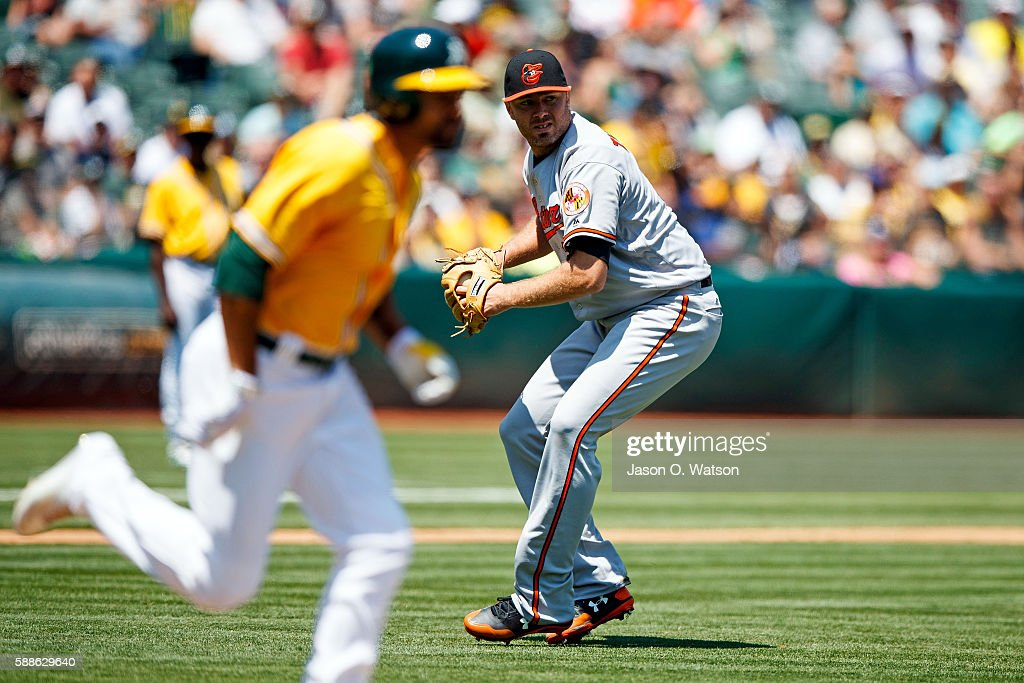 Chris Tillman #30 of the Baltimore Orioles throws to first base to force out Coco Crisp #4 of the Oakland Athletics during the third inning at the Oakland Coliseum on August 11, 2016 in Oakland, California. The Baltimore Orioles defeated the Oakland Athletics 9-6.
