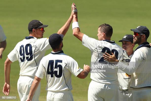 Chris Tremain Dan Christian and Peter Siddle celebrate with team mates of the VIC Bushrangers during day four of the Sheffield Shield match between...