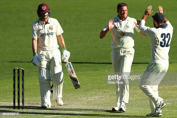 Chris Tremain of the Bushrangers celebrates dismissing Joe Burns of the Bulls during day two of the Sheffield Shield match between Queensland and...
