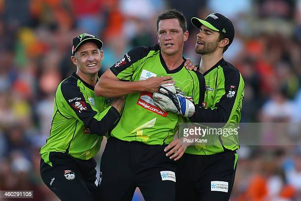 Chris Tremain of the Thunder is congratulated by Mike Hussey and Ryan Carters after dismissing Shaun Marsh of the Scorchers during the Big Bash...