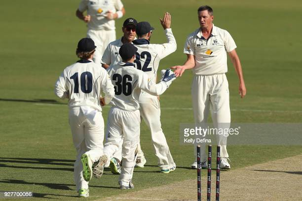 Chris Tremain of the VIC Bushrangers celebrates after taking a wicket with teammates Glenn Maxwell and Sebastion Gotch during day one of the...