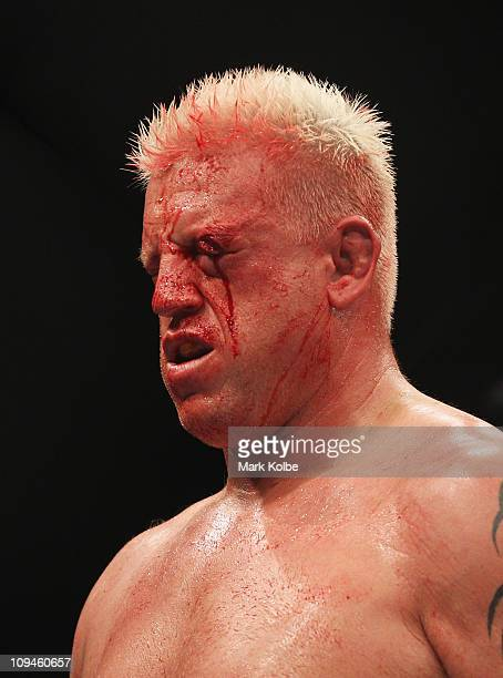 Chris Tuchscherer of the United States bleeds from a cut over his left eye while fighting Mark Hunt of Australia during their heavyweight bout as...