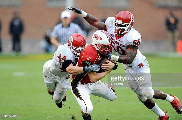 Chris Turner of the Maryland Terrapins is tackled by Ryan D'Imperio and Antonio Lowery of the Rutgers Scarlet Knights at Byrd Stadium on September 26...