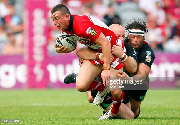Chris Tuson of Wigan Warriors is challenged by Danny Ward and Karl Temata of Harlequins RL during the Engage Super League match between Harlequins RL...