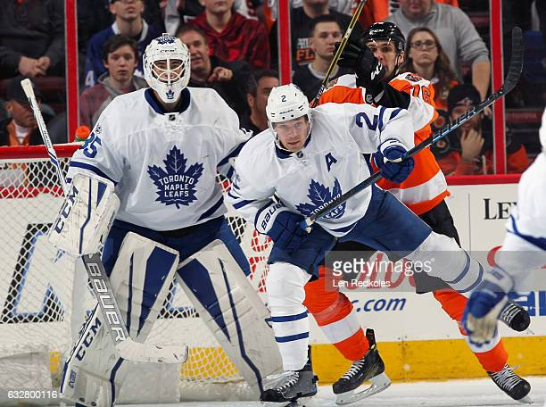 Chris VandeVelde of the Philadelphia Flyers battles for position in front of Curtis McElhinney of the Toronto Maple Leafs with Matt Hunwick on...