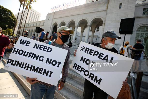 Chris Venn, left, and Michal Lindley, right, join people gather for The Right to REST without ARREST Rally and Press Conference on the steps of Los...