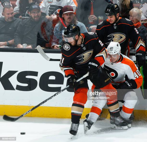 Chris Wagner and Kevin Bieksa of the Anaheim Ducks battle for the puck against Jordan Weal of the Philadelphia Flyers during the game on October 7...