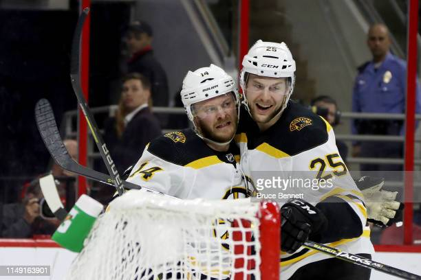Chris Wagner of the Boston Bruins celebrates with Brandon Carlo after scoring a goal on Curtis McElhinney of the Carolina Hurricanes during the...