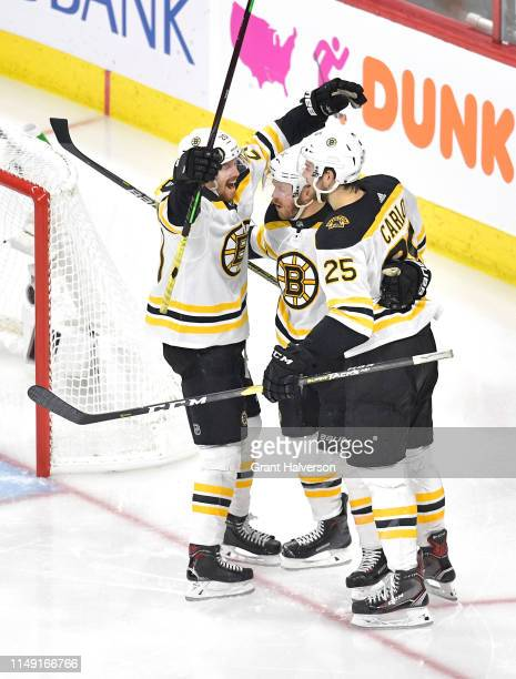 Chris Wagner of the Boston Bruins celebrates with Brandon Carlo and Joakim Nordstrom after scoring a goal on Curtis McElhinney of the Carolina...
