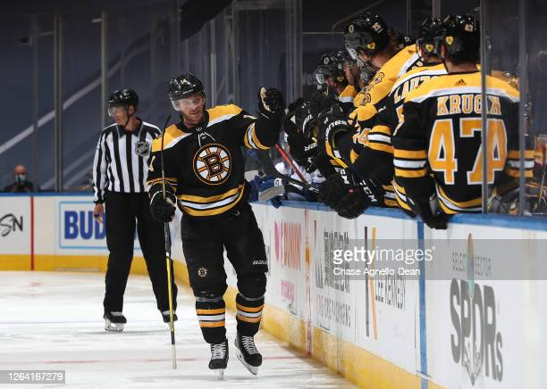 Chris Wagner of the Boston Bruins skates by the bench to celebrate with teammates after Wagner scored in the third period of a Round Robin game...
