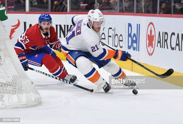 Chris Wagner of the New York Islanders skates with the puck under pressure from Victor Mete of the Montreal Canadiens in the NHL game at the Bell...