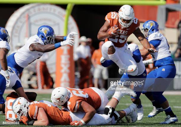 Chris Warren III of the Texas Longhorns leaps over defenders in the third quarter against the San Jose State Spartans at Darrell K Royal-Texas...