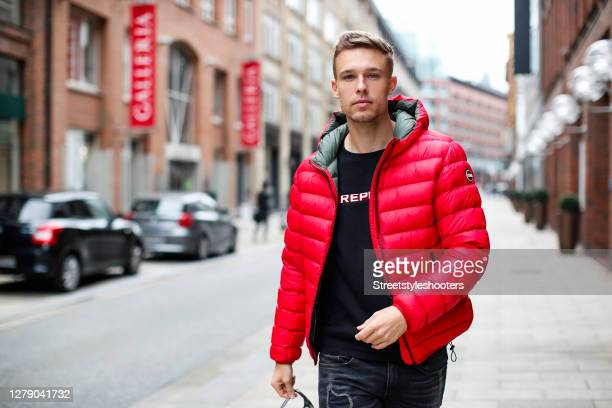 Chris Wascheck wearing a black sweatshirt with white logo print by Replay, a red jacket by Colmar and blue-grey denim jeans by Replay during a street...