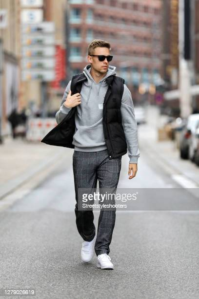 Chris Wascheck, wearing a grey hoodie by Axel Arigato, a black vest by Woolrich, dark grey checkered pants by Baldessarini, white sneaker by Nike and...
