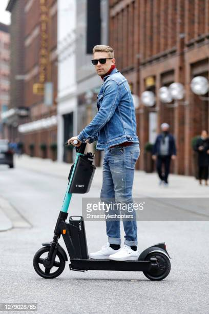 Chris Wascheck, wearing a jeans and a jeans jacket by Replay, a red turtleneck pullover by Brunello Cucinelli, white sneakers by Nike and sunglasses...