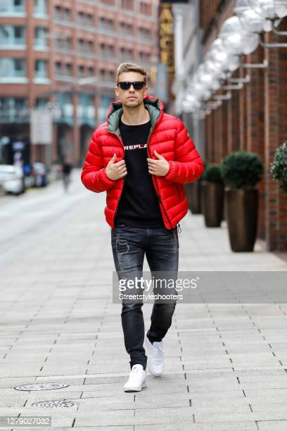 Chris Wascheck wearing sunglasses by Prada, a black sweatshirt with white logo print by Replay, a red jacket by Colmar, blue-grey denim jeans by...