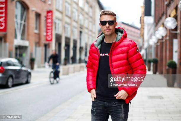 Chris Wascheck wearing sunglasses by Prada, a black sweatshirt with white logo print by Replay, a red jacket by Colmar and blue-grey denim jeans by...