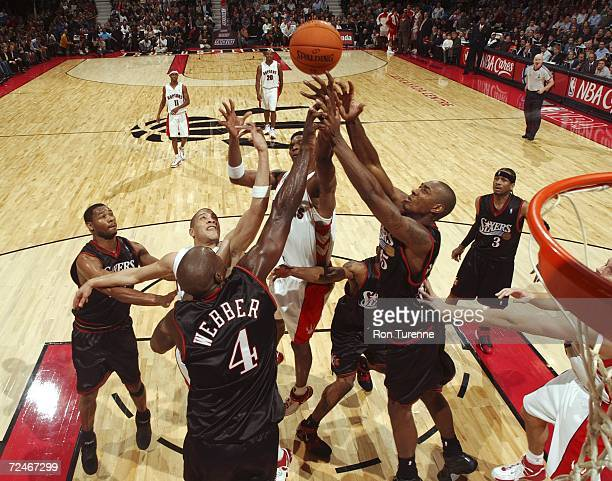 Chris Webber and Steven Hunter of the Philadelphia 76ers fight for the ball with Anthony Parker and Chris Bosh of the Toronto Raptors at the Air...