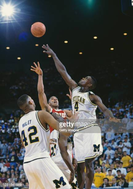 Chris Webber, Forward for the University of Michigan Wolverines and Jim Jackson, Guard for the Ohio State Buckeyes contest the ball over Eric Riley...
