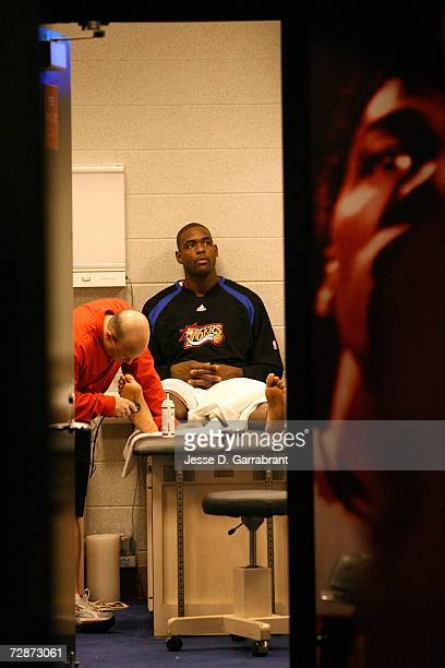 Chris Webber of the Philadelphia 76ers has his injured right foot and ankle attended to prior to the start of the game against the New York Knicks on...