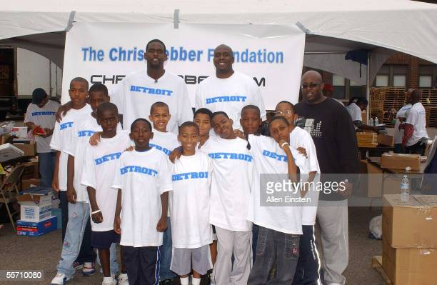 Chris Webber of the Philadelphia 76ers poses with young student volunteers during his book and school supply donation drive for the youngest victims...