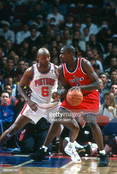 Chris Webber of the Washington Bullets backs in on Terry Mills of the Detroit Pistons during an NBA Basketball game circa 1995 at The Palace of...