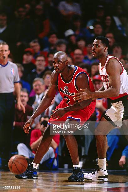 Chris Webber of the Washington Bullets dribbles against Buck Williams of the Portland Trail Blazers circa 1995 at the Veterans Memorial Coliseum in...