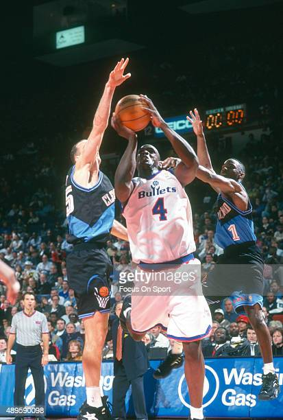 Chris Webber of the Washington Bullets looks to shoot over Danny Ferry and Terrell Brandon of the Cleveland Cavaliers during an NBA basketball game...