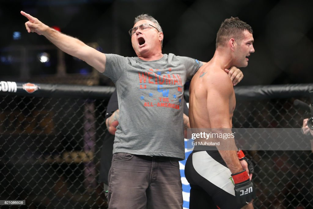 Chris Weidman (R) and father Charlie Weidman celebrate Weidman's submission win during his UFC Fight Night middleweight bout at the Nassau Veterans Memorial Coliseum on July 22, 2017 in Uniondale, New York.