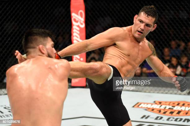 Chris Weidman kicks Kelvin Gastelum in their middleweight bout during the UFC Fight Night event inside the Nassau Veterans Memorial Coliseum on July...