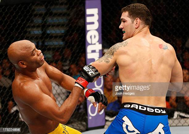 Chris Weidman looks on as Anderson Silva falls to the canvas after a punch in their UFC middleweight championship fight during the UFC 162 event...