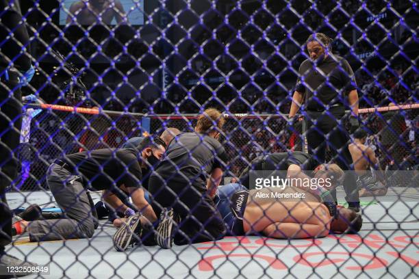Chris Weidman of the United States is attended to after breaking his leg on a kick attempt on Uriah Hall of Jamaica during UFC 261 at VyStar Veterans...