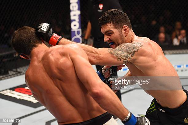 Chris Weidman punches Luke Rockhold in their UFC middleweight championship bout during the UFC 194 event inside MGM Grand Garden Arena on December 12...