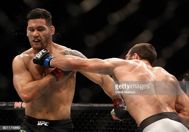 Chris Weidman takes a punch from Luke Rockhold in their middleweight title fight during UFC 194 at MGM Grand Garden Arena on December 12 2015 in Las...